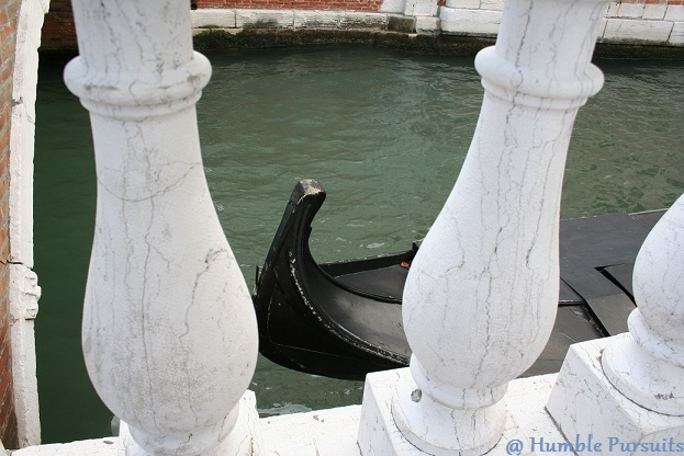 Gondola seen through Marble Pillars of a Venice Canal, Italy